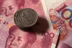 Банкноты и монеты китайского юаня. Пекин, 30 декабря 2010 года.  Центробанк Китая готов к внезапной атаке на юань на внешних рынках и может вмешаться, если разница между обменными курсами на материковом и внематериковом рынке станет дестабилизирующей, сказали источники, участвующие в обсуждении политики. REUTERS/Petar Kujundzic/Files