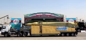 """Грузовик с ракетой """"Кадер H"""" проезжает мимо портрета аятоллы Али Хаменеи на параде в Тегеране 22 сентября 2015 года. Десятки сенаторов-республиканцев призвали президента США Барака Обаму в среду не снимать санкции с Ирана, говоря, что недавние испытания Тегераном баллистической ракеты показали """"вопиющее невыполнение его международных обязательств"""". REUTERS/Raheb Homavandi/TIMA"""