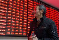 Un inversor sonríe al mirar a un tablero electrónico que muestra información bursátil, en una correduría en Nanjing, China, 17 de diciembre de 2015. Las acciones chinas repuntaron el jueves gracias a que el apetito por el riesgo mejoró después de que la Reserva Federal subió las tasas de interés por primera vez en casi una década, eliminando una de las principales fuentes de incertidumbre sobre la política del banco central estadounidense. REUTERS/China Daily   ATENCIÓN EDITORES - ESTA IMAGEN FUE PROVISTA POR UNA TERCERA PARTE.SÓLO DISPONIBLE PARA USO EDITORIAL. ESTA IMAGEN ES DISTRIBUIDA EXACTAMENTE COMO FUE RECIBIDA POR REUTERS,COMO UN SERVICIO A LOS CLIENTES