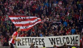 """Болельщики """"Атлетика"""" из Бильбао держат баннер """"Добро пожаловать, беженцы"""" на домашнем матче Лиги Европы против """"Аугсбурга"""". 17 сентября 2015 года. Около 991.000 беженцев и мигрантов прибыли в Европу по суше и морю в 2015 году, и в ближайшие дни их число достигнет миллиона, сообщила Международная организация по миграции (IOM) в пятницу. REUTERS/Vincent West"""