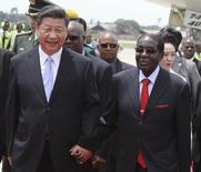 Chinese President Xi Jinping walks with Zimbabwean President Robert Mugabe on arrival for a state visit in Harare, Zimbabwe December 1, 2015. REUTERS/Philimon Bulawayo