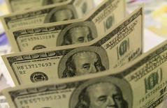 Billetes de 100 dólares estadounidenses, en un banco en Budapest, 8 de agosto de 2011. El dólar se debilitaba el lunes frente a una canasta de monedas en medio de escasas operaciones, mientras el euro se fortalecía luego de un resultado electoral indefinido en España que generaba incertidumbre sobre la estabilidad financiera del país ibérico. REUTERS/Bernadett Szabo