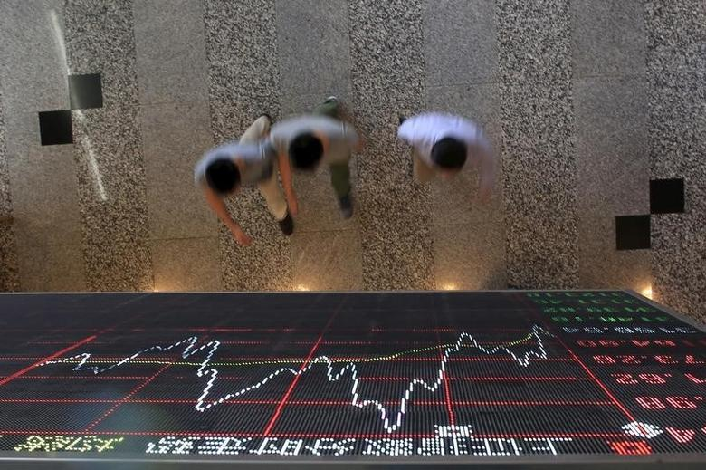 People walk under an electronic board showing stock information at the Shanghai Stock Exchange in Lujiazui Financial Area before the visit of Britain's Chancellor of the Exchequer George Osborne in Shanghai, China, September 22, 2015. REUTERS/Aly Song