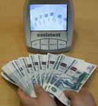 """Сотрудник банка проверяет рублевые купюры в Санкт-Петербурге 4 февраля 2010 года. Рубль ушел в минус против доллара и евро расчетами """"завтра"""" в пятничную биржевую сессию на фоне сокращения предложения валюты от корпораций. Текущая рыночная ликвидность понижена из-за закрытых в западное Рождество европейских и американских рынков, в связи с чем не проводятся и валютные торги расчетами """"сегодня"""". REUTERS/Alexander Demianchuk"""
