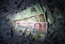 Южнокорейский вон, китайский юань и японская иена рядом с купюрой в 100 долларов.   REUTERS/Kim Hong-Ji