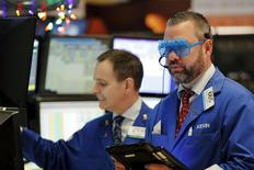 A trader wears plastic glasses to celebrate the last trading day of 2015 while working on the floor of the New York Stock Exchange shortly after the opening bell in New York December 31, 2015. REUTERS/Lucas Jackson