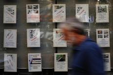 El precio medio de la vivienda nueva en España subió en 2015 un 2,9 por ciento registrando el primer repunte anual desde 2007, según datos difundidos el viernes por Sociedad de Tasación, que proyecta una continuación de la recuperación en 2016. En la imagen de archivo, un hombre pasa frente a una inmobiliaria con carteles de ofertas de pisos  en Madrid en septiembre de 2014. REUTERS/Susana Vera