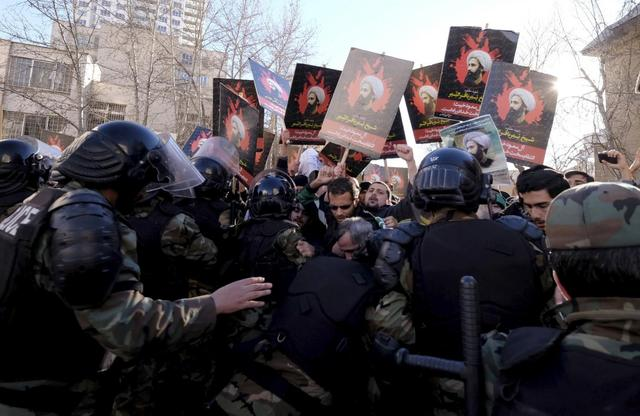 Protesters holding pictures of Shi'ite cleric Sheikh Nimr al-Nimr are pushed back by Iranian riot police during a demonstration against the execution of Nimr in Saudi Arabia, outside the Saudi Arabian Embassy in Tehran January, 3, 2016. REUTERS/Raheb Homavandi/TIMA