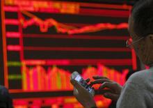 Un hombre revisa su celular frente a un tablero electrónico en una correduría en Pekín, China, 5 de enero de 2016. Las acciones de China subían el martes luego de que los reguladores financieros y el banco central adoptaron medidas agresivas para restaurar la confianza, un día después de un desplome que preocupó a los mercados globales. REUTERS/Kim Kyung-Hoon