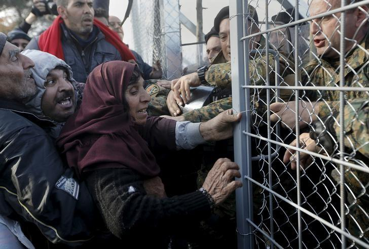 Syrian refugees struggle to enter Macedonia through a narrow border crossing as Macedonian policemen try to shut a metal gate near to the Greek village of Idomeni December 4, 2015. REUTERS/Yannis Behrakis