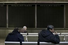 People sit in front of an electronic boarding that was turned off after trading was suspended, at a brokerage house, in Beijing, China, January 7, 2016.  REUTERS/Jason Lee