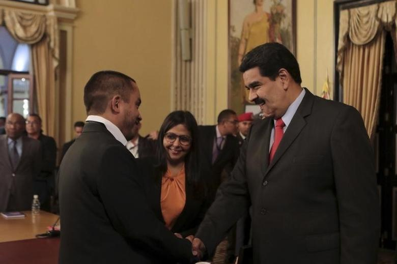 President Nicolas Maduro (R) and Venezuela's new Minister for Economy and Productivity Luis Salas shake hands during a meeting at Miraflores Palace in Caracas, in this handout picture provided by Miraflores Palace on January 6, 2016.  REUTERS/Miraflores Palace/Handout via Reuters