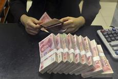 Funcionária conta notas de 100 iuans em agência de banco em Hefei, na China. 20/04/2015 REUTERS/Stringer