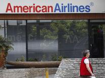 Una mujer camina junto a una oficina de American Airlines en Caracas, 17 de junio de 2014. American Airlines Group Inc dijo el martes que ha dado por perdidos más de 500 millones de dólares en ingresos retenidos en Venezuela debido a los controles cambiarios del país sudamericano. REUTERS/Carlos Garcia Rawlins