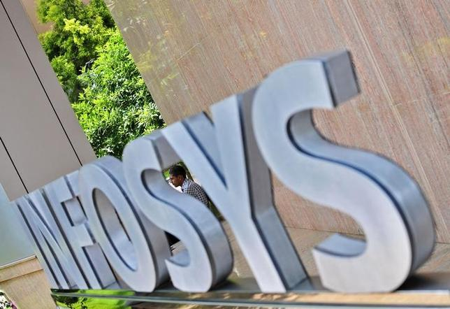 An employee is seen behind an Infosys logo at the company's campus in Bangalore September 23, 2014. REUTERS/Abhishek Chinnappa/Files