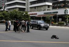 """Вооруженные ружьями полицейские в Джакарте рядом с лежащим на улице телом 14 января 2016 года. По меньшей мере шестеро погибли от взрывов и стрельбы в центре столицы Индонезии Джакарты, ответственность за которые взяли на себя джихадисты """"Исламского государства"""", несколько недель назад угрожавшие популярной среди туристов стране на юго-востоке Азии. REUTERS/Beawiharta"""