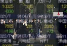 Personas se reflejan en un tablero electrónico que muestra la información de las acciones, afuera de una correduría en Tokio, Japón, 14 de enero de 2016. Las acciones japonesas bajaron el jueves, devolviendo la mayor parte de las ganancias de la jornada anterior, ya que la debilidad de los precios del petróleo aumentó los temores sobre una desaceleración económica global. REUTERS/Toru Hanai