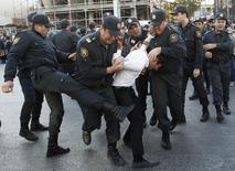 Полиция задерживает сторонника оппозиции в Баку 12 октября 2013. Полиция и солдаты задержали на этой неделе в Азербайджане 55 человек за несогласованные протесты, толчком к которым стало падение доходов населения на фоне девальвации маната вслед за удешевлением нефти. REUTERS/David Mdzinarishvili