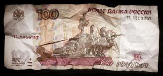 Сторублевая купюра. Москва, 11 января 2016 года. Рубль ускорил свое внутридневное снижение на фоне падения нефти Brent под отметку $30 за баррель, при этом котировки российской валюты приблизились к минимумам с середины декабря 2014 года. REUTERS/Maxim Zmeyev
