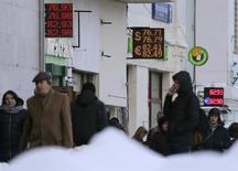 Люди у пунктов обмена валюты в Москве. 14 января 2016 года. Рубль в понедельник упал на новые 13-месячные минимумы, копируя динамику нефти, подешевевшую до значений осени 2003 года на фоне ожиданий роста её экспорта из Ирана, с которого в выходные были сняты экономические санкции. REUTERS/Maxim Shemetov