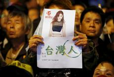 A supporter of Democratic Progressive Party (DPP) Chairperson and presidential candidate Tsai Ing-wen holds up a poster of Taiwanese K-pop singer Chou Tzuyu at their party headquarters as they wait for the results of the general elections January 16, 2016. REUTERS/Damir Sagolj