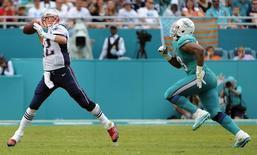 Jan 3, 2016; Miami Gardens, FL, USA; New England Patriots quarterback Tom Brady (12) throws a pass while chased by Miami Dolphins defensive end Derrick Shelby (79) in the third quarter at Sun Life Stadium. Mandatory Credit: Robert Duyos-USA TODAY Sports