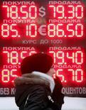 Женщина у пункта обмена валюты в Москве. 18 января 2016 года. Рубль в плюсе на торгах вторника, копируя восходящую динамику нефти, а также сырьевых и развивающихся валют после падения предыдущих дней в ожидании роста нефтяного экспорта из Ирана, с которого в выходные были сняты экономические санкции. REUTERS/Sergei Karpukhin