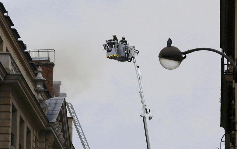French firefighters work to tackle a fire on the roof of the luxury Ritz Paris hotel at the Place Vendome, central Paris, January 19, 2016.    REUTERS/Jacky Naegelen
