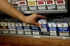 El fabricante de tabaco Altadis, la división española de Imperial Tobacco, anunció el martes un plan de reestructuración que contempla el cierre de su fábrica de cigarrillos de La Rioja y ajustes en las áreas de finanzas y  ventas del grupo. En esta imagen de archivo, una trabajadora de un estanco coge un paquete de cigarrillos en Madrid el 19 de junio de 2008. REUTERS/Juan Medina