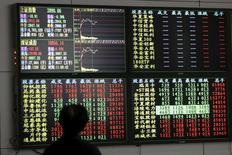 Un inversor mira un tablero electrónico que muestra información bursátil, en una correduría en Shanghái, China, 18 de enero de 2016. El Fondo Monetario Internacional recortó sus pronósticos de crecimiento global el martes por tercera vez en menos de un año, citando una fuerte desaceleración del comercio en China y precios débiles de las materias primas que están afectando a Brasil y a otros mercados emergentes. REUTERS/Aly Song