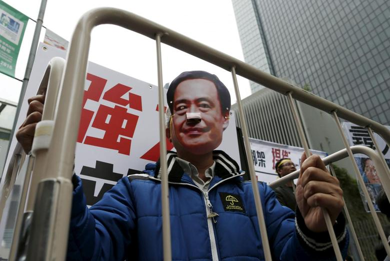 A demonstrator wears a mask depicting Causeway Bay Books shareholder Lee Bo during a protest over the disappearance of booksellers, in Hong Kong, China January 10, 2016. REUTERS/Tyrone Siu