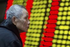 Un inversor mira un tablero electrónico que muestra información bursátil, en una correduría en Nanjing, China, 13 de enero de 2016. Las acciones chinas cayeron más de un 1 por ciento el miércoles, aunque los rumores sobre un estímulo inminente ofrecieron cierto apoyo en el contexto de un nuevo declive en los precios del petróleo que golpeó a los mercados bursátiles en todo el mundo. REUTERS/China Daily