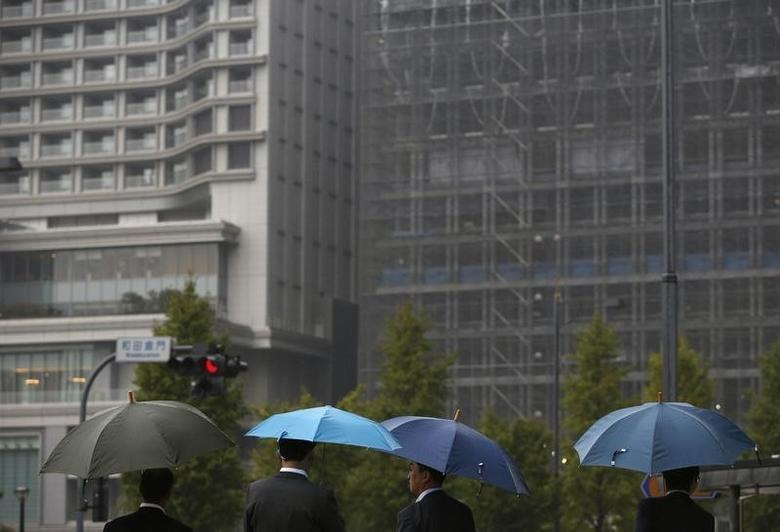 Businessmen holding umbrellas wait for a traffic signal in front of a high-rise hotel and a building under construction, in Tokyo October 29, 2013.  REUTERS/Issei Kato