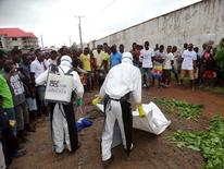 Healthcare workers prepare to remove the body of a man suspected of carrying Ebola in Monrovia, Liberia, July 17, 2015. REUTERS/James Giahyue