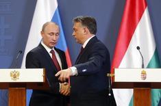 Президент России Владимир Путин пожимает руку премьер-министру Венгрии Виктору Орбану (справа) на пресс-конференции в Будапеште 17 февраля 2015 года. Венгрия не ждет, что Россия откажется от финансирования расширения атомной электростанции Пакш, сказал венгерский чиновник. REUTERS/Laszlo Balogh