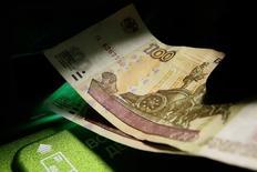 Клиент банка вставляет 100-рублевые купюры в банкомат в Красноярске. 11 января 2016 года. Рубль дорожает утром пятницы благодаря существенному росту нефтяных цен; в пользу рубля и закрытие длинных валютных позиций, как в условиях коррекции нефти, так и с целью фиксации прибыли перед выходными. REUTERS/Ilya Naymushin