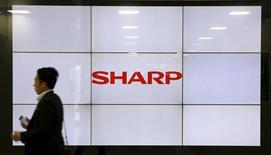 Мужчина проходит мимо экрана с логотипом Sharp в Токио. 30 октября 2015 года. Японский государственный фонд и кредиторы Sharp могут договориться о новом плане помощи для производителя дисплеев на сумму примерно в 650 миллиардов иен ($5,5 миллиарда) к следующим выходным, сказали источники, непосредственно знакомые с ситуацией, в пятницу. REUTERS/Toru Hanai