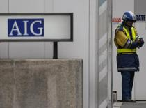 A construction worker stands near an AIG logo in Tokyo March 3, 2009. REUTERS/Issei Kato