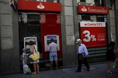 Banco Santander registró un descenso del 98 por ciento en el beneficio atribuible del cuarto trimestre castigado por unos cargos de 1.435 millones de euros en unos resultados que también destacaron por la mejora de su ratio de solvencia. En la imagen de archivo, personas usando cajeros en una sucursak de Santander en Madrid. REUTERS/Susana Vera