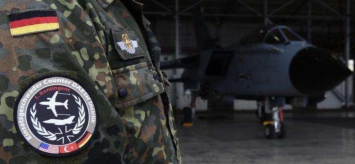 A soldier of the German Armed Forces Bundeswehr wears a patch of the combat wing (Einsatzgeschwader) Counter DAESH Incirlik next to a German Tornado jet in a hangar before a statement of the German and Turkish defence ministers at the air base in Incirlik, Turkey, January 21, 2016. REUTERS/Tobias Schwarz/Pool