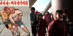 North Korean children walk past a standing signboard depicting ice hockey in Pyongyang, North Korea, in this undated handout picture. REUTERS/Michael Spavor/Handout via Reuters