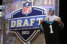 Quarterback Cam Newton of Auburn University poses with a jersey after being selected as the first overall pick by the Carolina Panthers in the 2011 NFL football Draft in New York, April 28, 2011.  REUTERS/Jessica Rinaldi