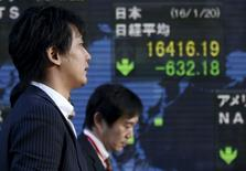 Unos hombres caminan junto a un tablero electrónico que muestra el índice Nikkei de Japón, afuera de una correduría en Tokio. 20 de enero de 2016. Las acciones japonesas cayeron en una sesión volátil el jueves luego de que la debilidad de los precios del petróleo y el temor a una desaceleración mundial siguieron minando la confianza.  REUTERS/Toru Hanai
