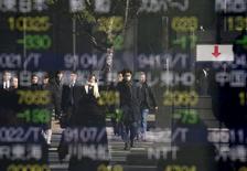 Personas se reflejan en un tablero electrónico que muestra información bursátil, afuera de una correduría en Tokio, Japón. 14 de enero de 2016. Las acciones japonesas cayeron el martes luego de que los inversores recogieron ganancias de un repunte reciente impulsado por la decisión del Banco de Japón de adoptar tasas de interés negativas la semana pasada. REUTERS/Toru Hanai