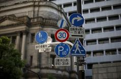 Traffic signs are seen in front of Bank of Japan (BOJ) buildings in Tokyo June 24, 2015. REUTERS/Toru Hanai