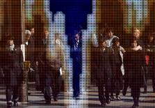 Peatones se reflejan en un tablero electrónico que muestra la gráfica de fluctuación reciente entre el yen japonés y el dólar estadounidense, afuera de una correduría en Tokio, Japón, 4 de febrero de 2016. Las bolsas de Asia subían levemente el viernes y el dólar se tambaleaba antes de un reporte de datos de empleo en Estados Unidos que podría proporcionar pistas sobre la perspectiva de la política monetaria de la Reserva Federal. REUTERS/Yuya Shino