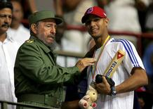 Then-Cuban President Fidel Castro (L) hands out a baseball bat to Cuban player Yulieski Gourriel in Havana in this March 21, 2006 file photo. REUTERS/Claudia Daut/Files