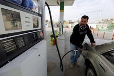 Мужчина заправляет автомобиль на АЗС в Багдаде. 26 января 2016 года. Управление энергетической информации США (EIA) снизило прогноз роста мирового потребления нефти в этом году. REUTERS/Ahmed Saad