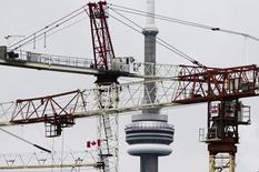 Construction cranes are seen in front of the CN Tower in Toronto December 5, 2012. REUTERS/Mark Blinch