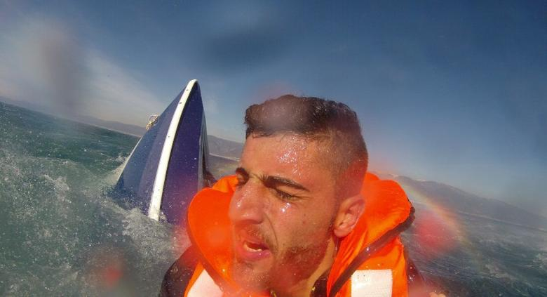 A migrant, identified as 20-year old Pelen Hussein from Syria, with a capsized boat in the background, is rescued by a member of the Turkish Coast Guard Air Command in the Aegean Sea off the waters of Edremit bay, Turkey February 8, 2016, in this handout photo provided by the Turkish Coast Guard Command. REUTERS/Turkish Coast Guard Command/Handout via Reuters